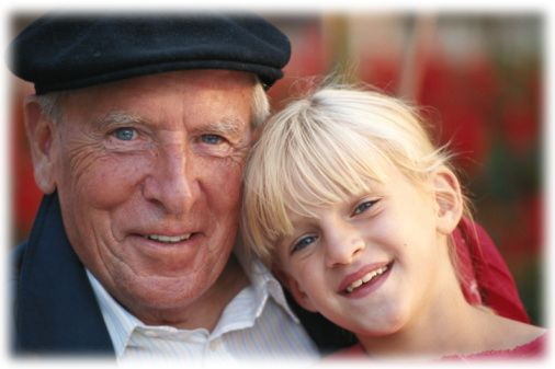 Grandfather with granddaughter (6-7) smiling, portrait